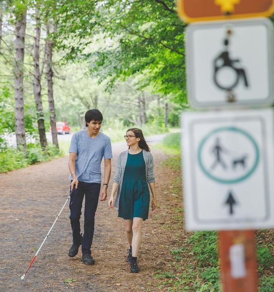 Personne aveugle guidée dans un parc