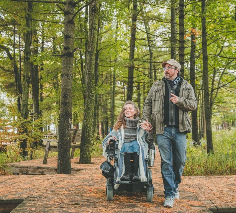 Personne en fauteuil et son accompagnateur dans les bois