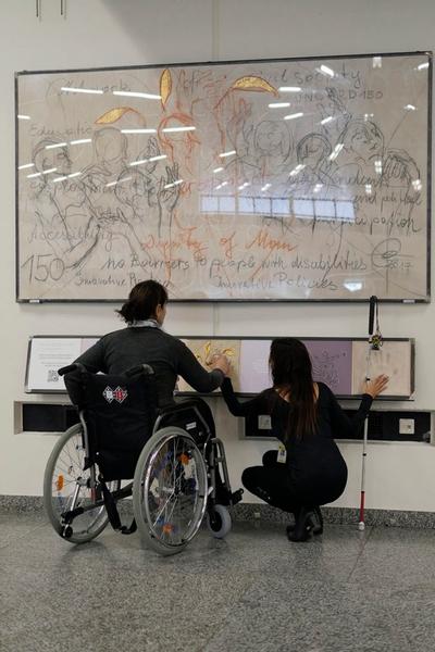 Personne en fauteuil roulant explorant la reproduction tactile des éléments d'une toile