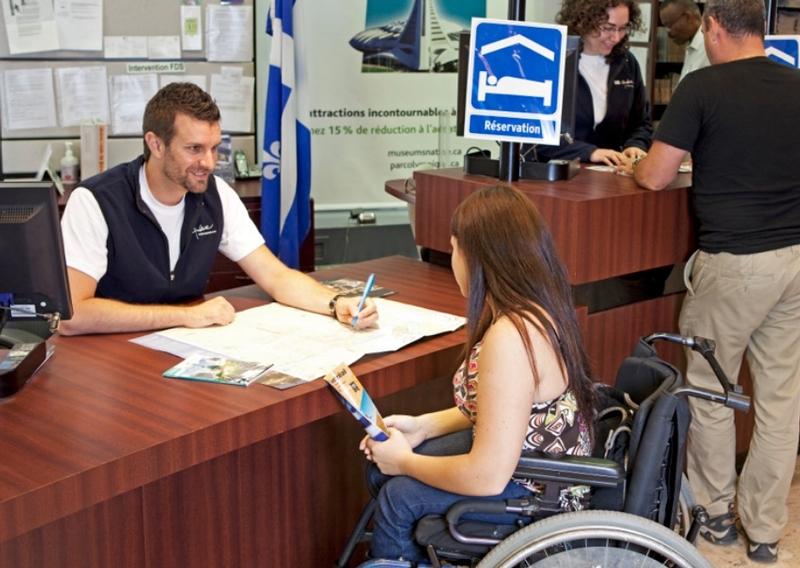 Personne en fauteuil discutant à un bureau d'information touristique