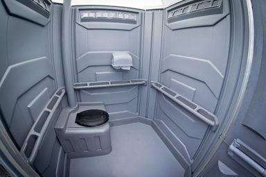 Intérieur gris d'une toilette chimique accessible. Grand espace, barre d'appui.